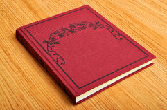 Red book. Beautiful red hardcover book on wooden floor Royalty Free Stock Images