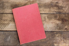 Red book on the background of rough planks. Stock Photos