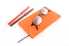 Red book, black glasses and markers Royalty Free Stock Photography