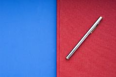 Red book on a blue background. A stricking image of a silver pen on a bright red book on a blue background royalty free stock photography