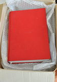 Red book in brown paper box Stock Photos