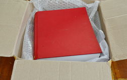 Red book in brown paper box Royalty Free Stock Image