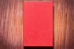A red book on a brown table. A red book on a table of a brown color Stock Image