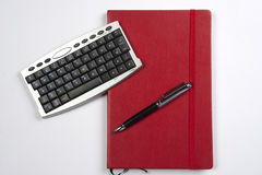 Red book and calculator. A office book with a pen and mini keyboard royalty free stock images