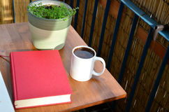 Red book, cup of coffee and green plant in flowerpot on small balcony table Stock Photos
