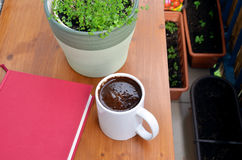 Red book, cup of coffee and green plant in flowerpot on small balcony table Royalty Free Stock Image
