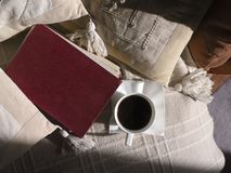 Coffee And Book. Red book and cup of coffee on a sofe covered with blanket and pillows, above view Royalty Free Stock Image