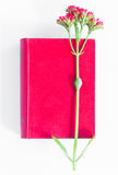 Red book and flower. On book against white background Stock Images