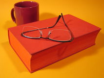 Red Book And Glasses III. Red book with glasses and a dark red cup in the background Royalty Free Stock Photos