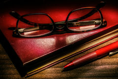Red book with glasses and pen Royalty Free Stock Photo