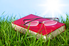 Red book on grass with spectacles. Royalty Free Stock Photos