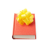 Red book isolated. Red gift book with the yellow decorational bow over it, composition isolated over the white background Royalty Free Stock Images