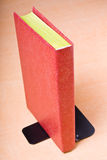 Red book leaning on bookend Stock Photos