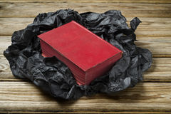 Red book. An old red book, black paper on a wooden table Royalty Free Stock Photo