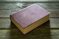 Red book. An old red book on a wooden table Royalty Free Stock Photo