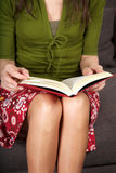 Red book over woman knees Royalty Free Stock Image