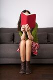 Red book on sitting woman face Royalty Free Stock Photography