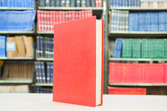 Red book standing on table with bookshelf in background Royalty Free Stock Image