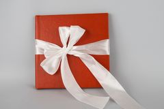 Red book with white ribbon. Red gift on a white background. Photo album. Orange notebook stock photography