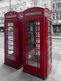 Red booths in London. Iconic red telephone booths in London. Selective colour filter applied Royalty Free Stock Photo