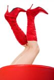 Red boots. Woman in red boots sitting on the red chair, studio shot Stock Photography