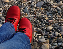 Red boots. Legs in red shoes on a pebble beach sea Stock Photo