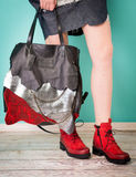 Red boots on woman legs and handbag Stock Photo