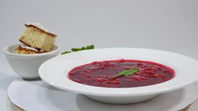 Red Borsch with meat in plate. A delicious red borscht with sour cream and herbs on a white plate. Traditional Ukrainian stock footage