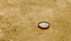 Red bottle cap on dirt Royalty Free Stock Images