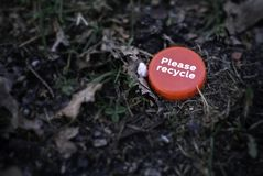 Red bottle cap with `Please recycle` message lying ironically on the grass ground in the middle of a park. Recycling concept. royalty free stock photo