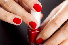 Red bottle of nail polish in hands Stock Image