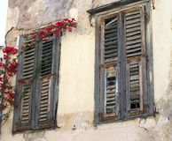 Red Bougainvillea Growing Across Wooden Window Shutters, Plaka, Athens, Greece. An historic original house in the Plaka Precinct, Athens, Greece, with red stock image