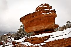 A red boulder is balanced on a mountain in a snowy winter scene. royalty free stock image