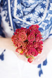 Red  bouquet of blooming roses in the hands Royalty Free Stock Image