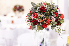 Red bouquet of greenery and roses on the high vase Royalty Free Stock Image