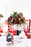 Red bouquet of greenery and roses on the high vase as a part of Royalty Free Stock Photography