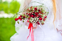 Red bouquet in hands of the bride. Wedding bouquet of red roses and leaves Stock Photography