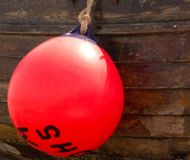 Red Bouy against a wooden boat. Red Bouy with black lettering resting against a wooden weathered boat royalty free stock image
