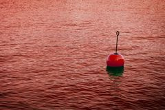 Red bouy on a calm bloody lake - concept image with copy space.  royalty free stock photos