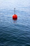 Red bouy on a calm lake Stock Photo