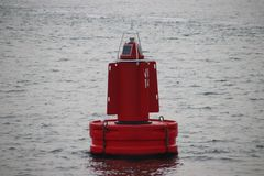 Red bouy on the Nieuwe Waterweg at the harbor of Rotterdam to mark the shipping route. Red bouy on the Nieuwe Waterweg at the harbor of Rotterdam to mark the stock images