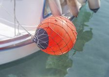 Red bouy tied at white fishing boat tied on marine dock. And sea water stock photo