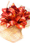 Red Bow with Gold Stars. Round red bow with golden stars on gold netting Royalty Free Stock Photography