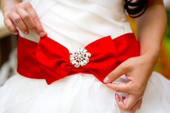 Red bow with brooch on wedding dress in hands of bride. Red or crimson bow with pearl brooch on white wedding dress in hands of bride Stock Image