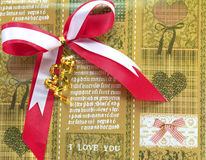 Red bow on brown Gift wrapping paper. Shiny red satin ribbon on Brown Gift wrapping paper Stock Image