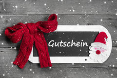 Red bow on chalk board with Voucher - coupon. Message on snowflake design, grey wooden background - for christmas Stock Images