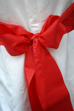 Red Bow Closeup. Closeup detail of a red bow decorating a white linen wedding chair. Also appropriate for holiday, Christmas, or other type of celebration Royalty Free Stock Photo