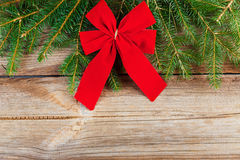 Red bow and fir tree branch on wooden board Royalty Free Stock Image