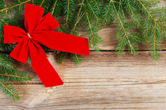 Red bow and fir tree branch on wooden board Royalty Free Stock Photography