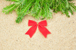 Red bow and fir tree on the sand Stock Photos
